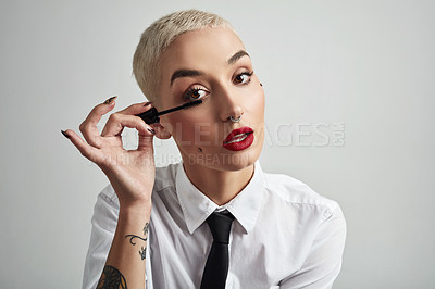 Buy stock photo Portrait of an attractive young businesswoman putting on mascara against a grey background
