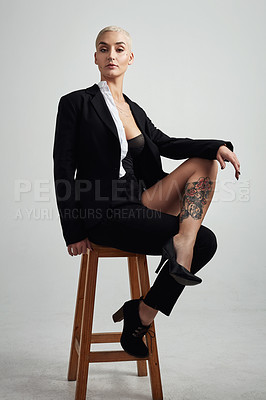 Buy stock photo Full length shot of an attractive young businesswoman in lingerie sitting on a stool against  a grey background