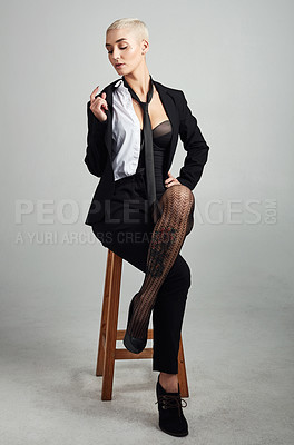 Buy stock photo Full length shot of an attractive young businesswoman sitting on a stool against  a grey background