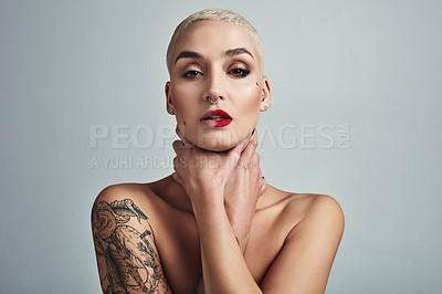 Buy stock photo Portrait of an attractive young woman choking herself with her hands against a grey background