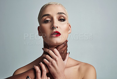 Buy stock photo Portrait of an attractive young woman posing with her throat being choked by an unrecognizable man against a grey background