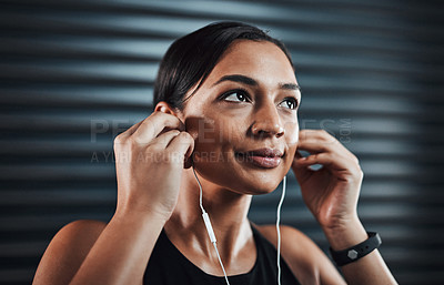 Buy stock photo Shot of a sporty young woman listening to music while exercising against a dark background