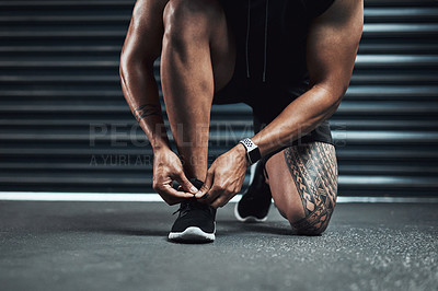 Buy stock photo Closeup shot of a sporty man tying his shoelaces while exercising against a dark background