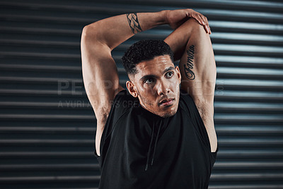 Buy stock photo Shot of a sporty young man stretching against a dark background