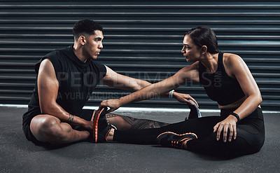 Buy stock photo Shot of two sporty young people exercising together against a dark background