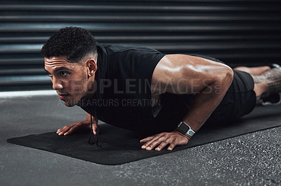 Buy stock photo Shot of a sporty young man doing pushup exercising
