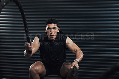 Buy stock photo Shot of a sporty young man exercising with battle ropes against a dark background