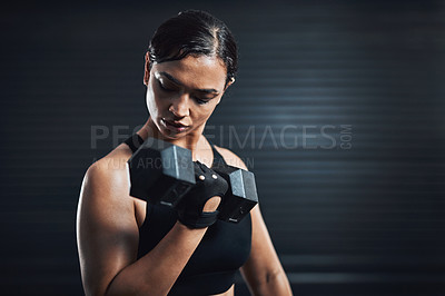 Buy stock photo Shot of a sporty young woman exercising with dumbbells against a dark background