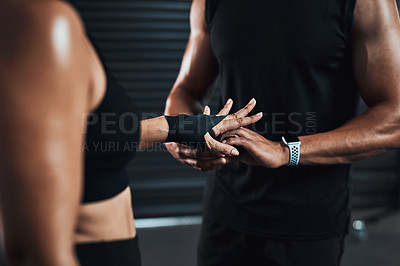 Buy stock photo Closeup shot of a woman getting her hands wrapped by her fitness trainer against a dark background