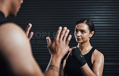 Buy stock photo Shot of a sporty young woman working out with her boxing trainer