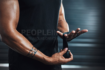 Buy stock photo Closeup shot of a sporty man wrapping his hands against a dark background