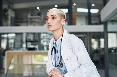 Buy stock photo Shot of a young doctor looking thoughtful while standing in a hospital