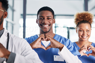 Buy stock photo Portrait of a group of medical practitioners making a heart shape with their hands in a hospital