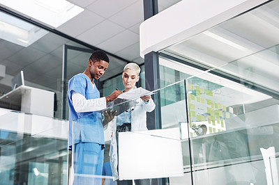 Buy stock photo Shot of two medical practitioners going over paperwork in a hospital
