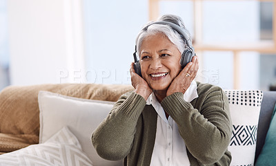 Buy stock photo Shot of a senior woman wearing headphones while listening to music at home