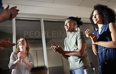 Buy stock photo Cropped shot of a diverse group of businesspeople standing together and clapping in the office at night