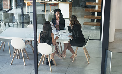 Buy stock photo High angle shot of three young businesswoman sitting in the boardroom during a management meeting