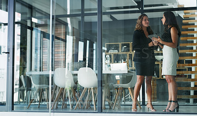 Buy stock photo Full length shot of two attractive young businesswoman talking while standing in their office