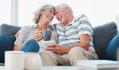 Buy stock photo Shot of a senior couple enjoying a relaxing coffee break on the sofa at home