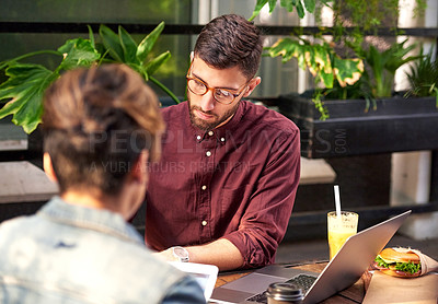 Buy stock photo Shot of two young businesspeople having a meeting and working together at an outdoor cafe