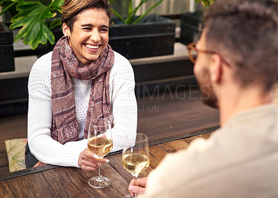 Buy stock photo Shot of an affectionate young couple relaxing and enjoying a glass of wine together at an outdoor cafe