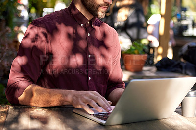 Buy stock photo Shot of an unrecognizable businessman using his laptop while relaxing at an outdoor cafe