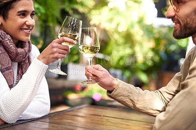 Buy stock photo Shot of an affectionate young couple sharing a toast while enjoying themselves at an outdoor cafe
