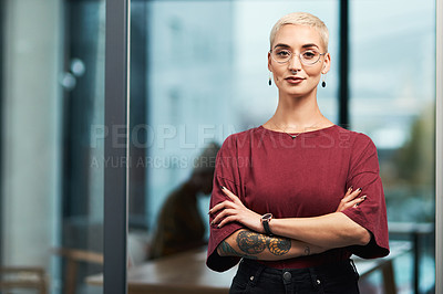 Buy stock photo Cropped portrait of an attractive young businesswoman wearing spectacles and standing alone in her office with her arms folded