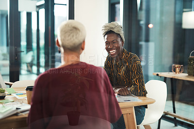 Buy stock photo Cropped shot of an attractive young businesswoman sitting and laughing with her female colleague in the office