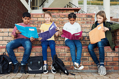 Buy stock photo Shot of a group of children reading books outside on school grounds