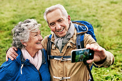 Buy stock photo Shot of a senior couple taking a selfie while going for a hike in nature