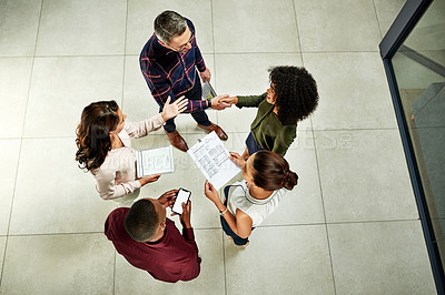 Buy stock photo High angle shot of a diverse group of businesspeople shaking hands before working with technology and documents in the office