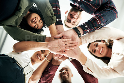 Buy stock photo Low angle shot of a diverse group of businesspeople standing and placing their hands in the middle of the circle