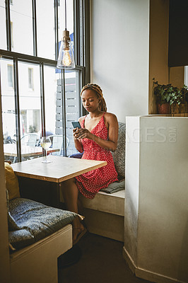 Buy stock photo Full length shot of an attractive young woman using her cellphone while enjoying a glass of wine inside a cafe