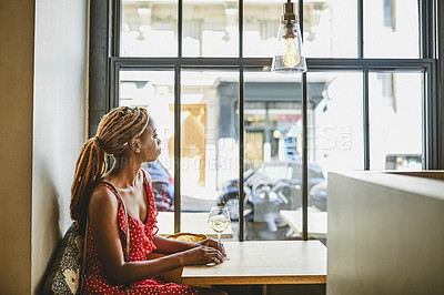 Buy stock photo Shot of an attractive young woman looking thoughtful while enjoying a glass of wine at a cafe