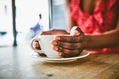 Buy stock photo Closeup shot of an unrecognizable woman enjoying a warm cup of coffee in a cafe