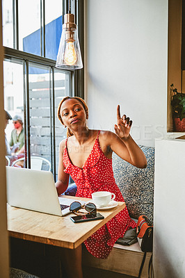 Buy stock photo Shot of an attractive young woman working on her laptop and calling for a barista at a cafe
