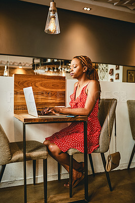 Buy stock photo Full length shot of an attractive young using her laptop while relaxing inside a cafe