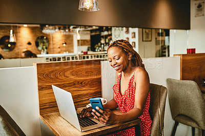 Buy stock photo Shot of an attractive young woman using her laptop and cellphone inside a cafe