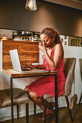 Buy stock photo Full length shot of an attractive young woman suffering from a headache while working on her laptop inside a cafe