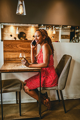 Buy stock photo Full length shot of an attractive young woman answering her cellphone while enjoying a glass of wine inside a cafe