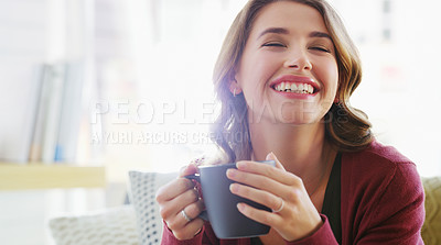 Buy stock photo Cropped shot of an attractive young woman sitting on her living room couch and enjoying a cup of coffee