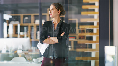 Buy stock photo Cropped shot of an attractive young businesswoman standing alone in her office with her arms folded