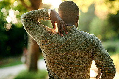 Buy stock photo Rearview shot of a sporty young man suffering from a sports injury outdoors