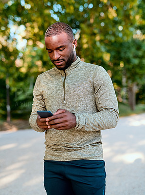 Buy stock photo Shot of a sporty young man using his cellphone while out for a workout