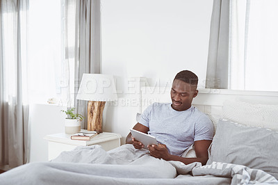 Buy stock photo Shot of a handsome young man using a digital tablet while lying in bed