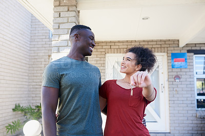 Buy stock photo Cropped shot of a happy young couple holding up the keys to their new home