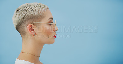 Buy stock photo Studio shot of an attractive young woman with piercings posing against a blue background
