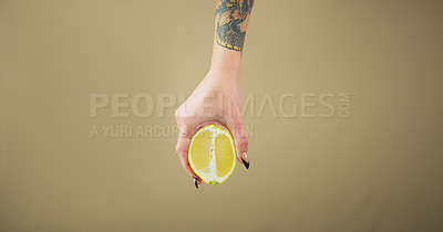 Buy stock photo Studio shot of an unrecognizable woman holding a lemon slice against a brown background