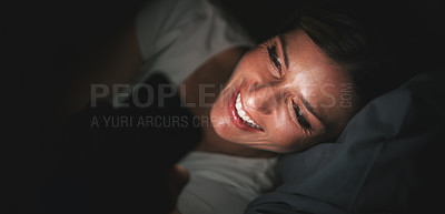 Buy stock photo Shot of a cheerful young woman using her cellphone while lying in bed late at night